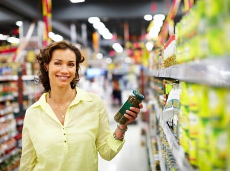 Portrait of smiling woman at supermarket holding jar of pickle